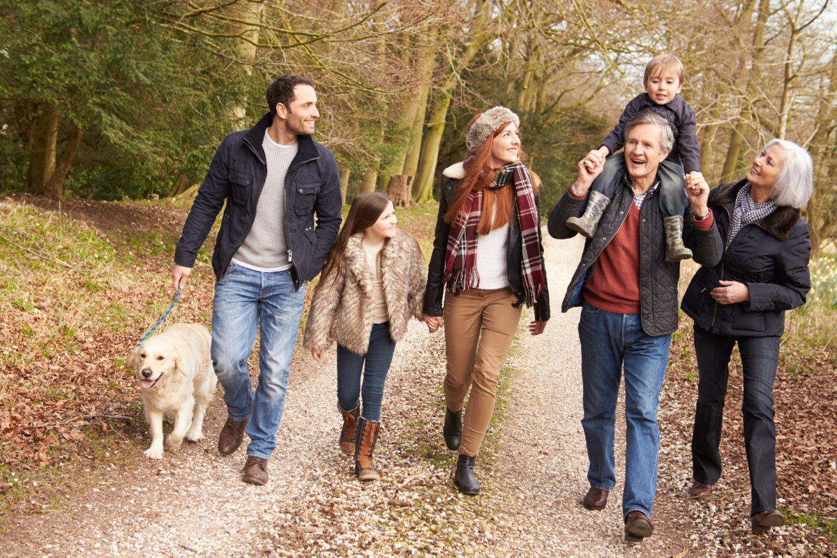 A photograph of a family walking along a country path; Golden Charter Funeral Plans offer peace of mind.