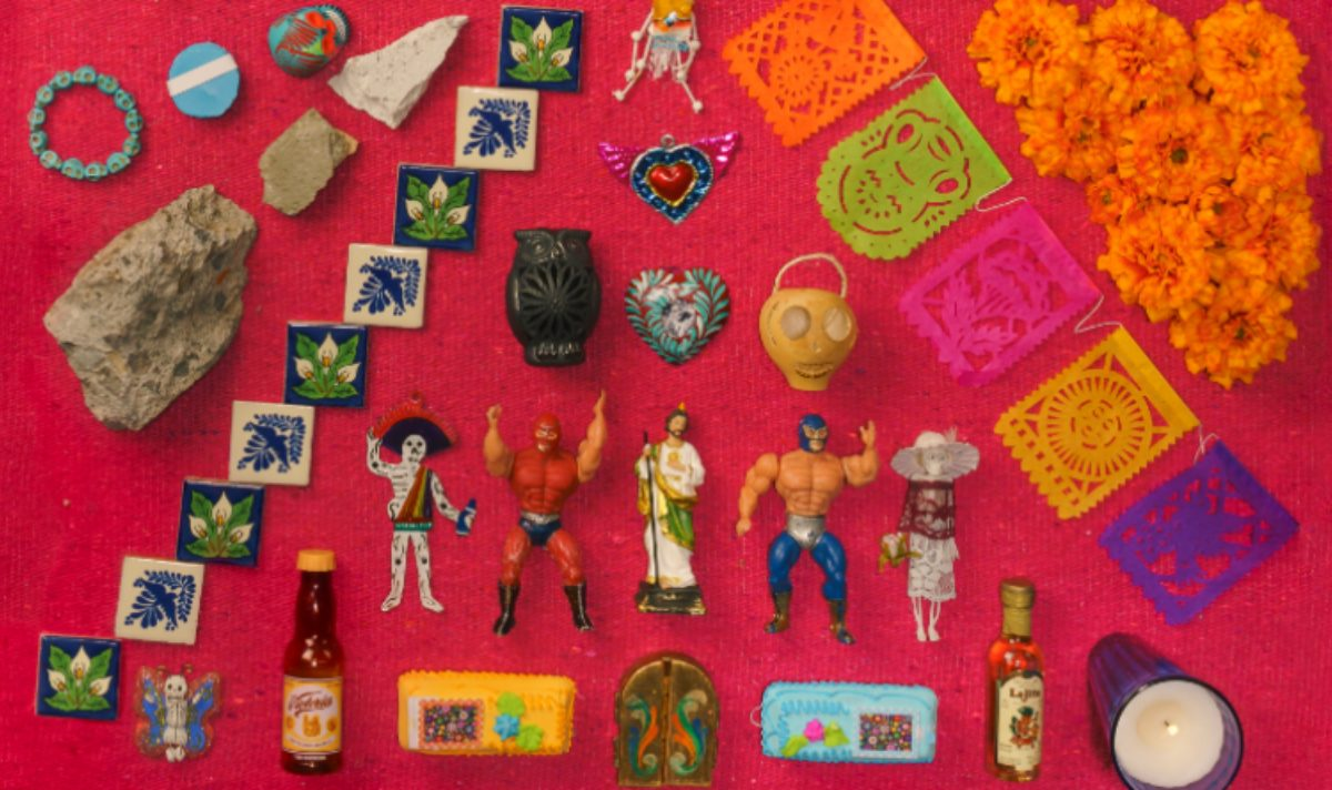 A selection of small plastic toys, sugar cakes, paper bunting, rocks, marigold flowers, coloured beads and coloured tiles to decorate an Ofrenda