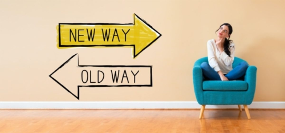 "Two arrows (one above the other) saying ""New Way"" and ""Old Way"" and a young woman, sitting in an armchair (situated to the right of the arrows), looking quizzical."