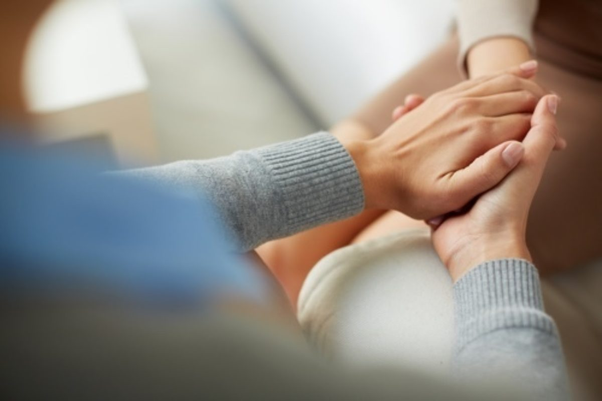 A picture of a pair of hands gently clasping another pair of hands